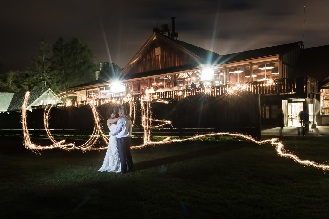 Photo of a bride and groom with the word LOVE in sparklers at Snow Trails Ski Resort