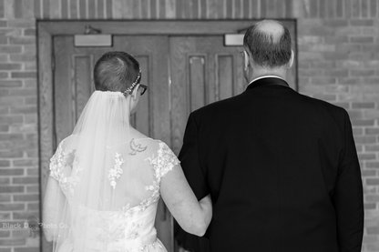 A wedding photo of a bride about to walk down the aisle with her father