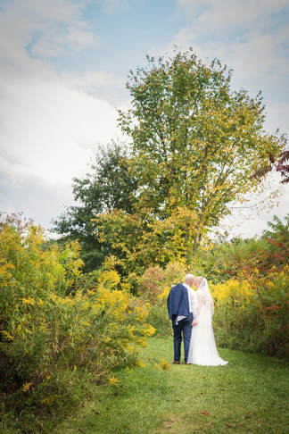 Akron Wedding Photo of a bride and groom in wild flowers.